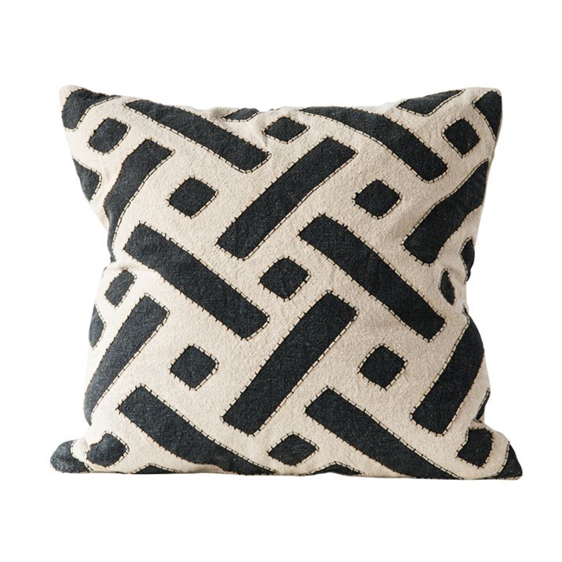 White pillow with geometric black shapes stitched atop