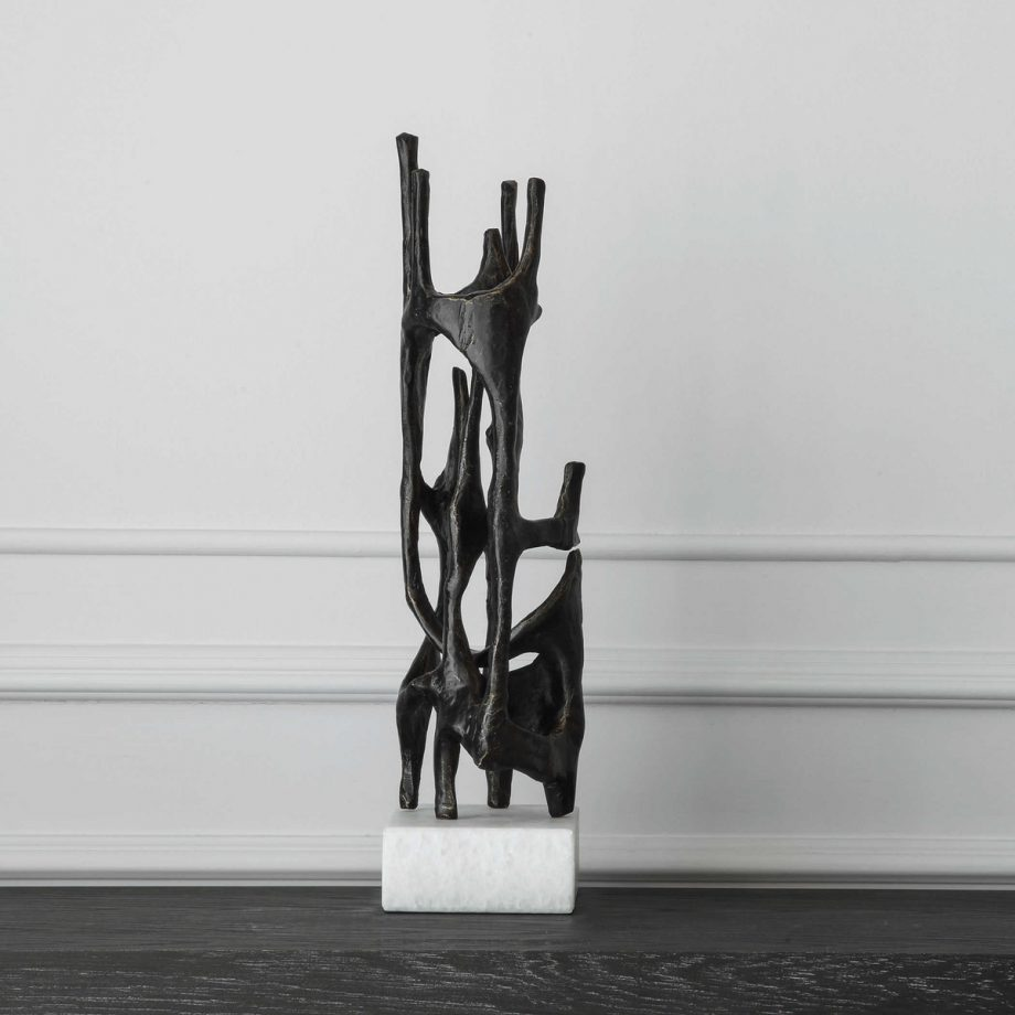vertical black metal architectural sculpture on white marble base