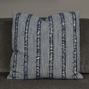 blue striped pillow with lines of fringe