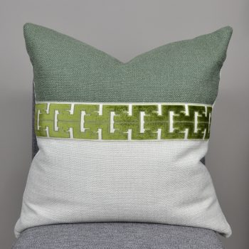 green and white pillow with green greek key stripe