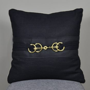 black pillow with gold buckle clasp